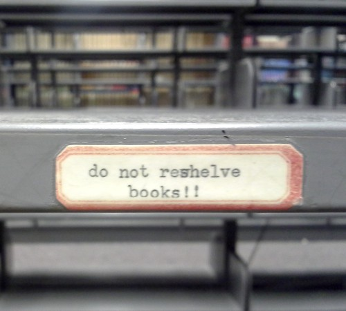 """Photo of sign taped to library shelf that says: """"Do not reshelve books!!"""""""