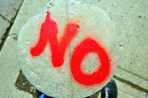 "photo of the word ""no"" spraypainted on a concrete pillar"