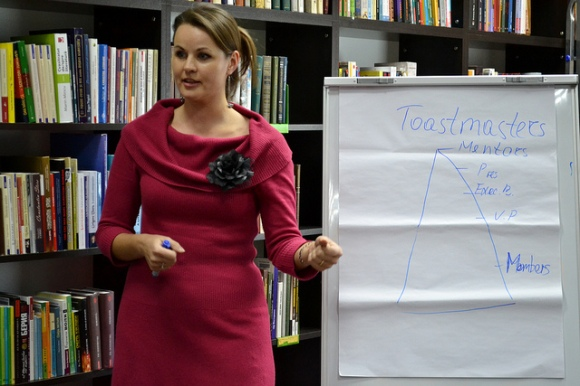 photo of a woman speaking in front of library bookshelves with a flipchart with Toastmasters organization