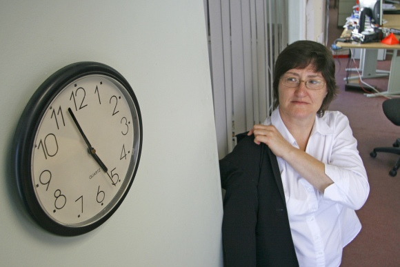 photo of a woman putting on a jacket under a wall clock showing 5pm