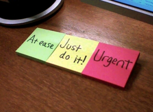 """Group of post-it notes with handwritten: """"At ease"""", """"Just do it!"""" and """"Urgent"""""""
