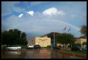 photo of blue skies, a rainbow, and america flags over the library building
