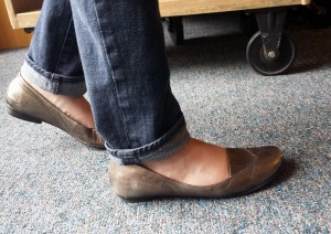 photo of walking feet with wheels of library cart in background