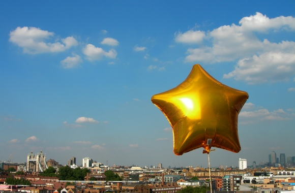 Photo of a star-shaped helium balloon floating over London cityscape