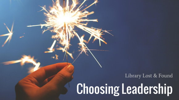 "hand presenting a lit sparkler with title ""Library Lost & Found: Choosing Leadership"""
